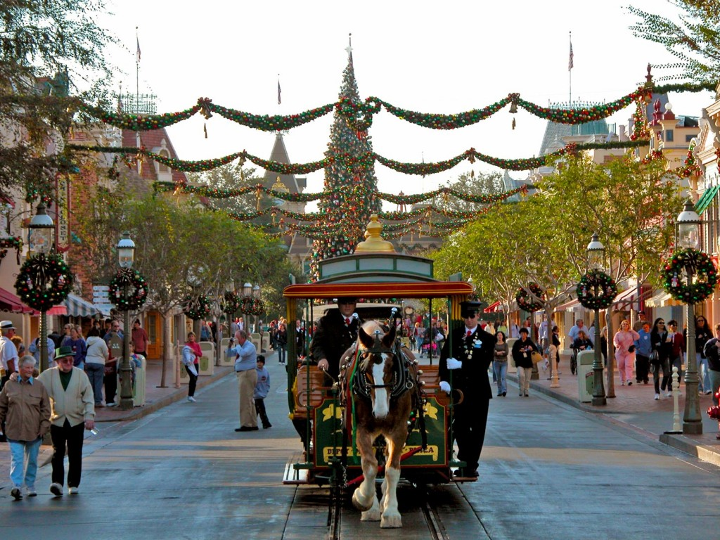 A look from the Hub towards the entrance shows the Disneyland Christmas tree in Town Square and holiday garland strung between the shops of Main Street.